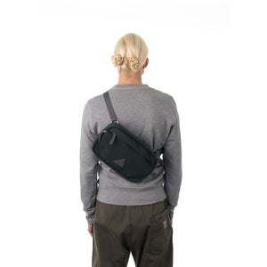 Woman wearing grey bumbag across across back.