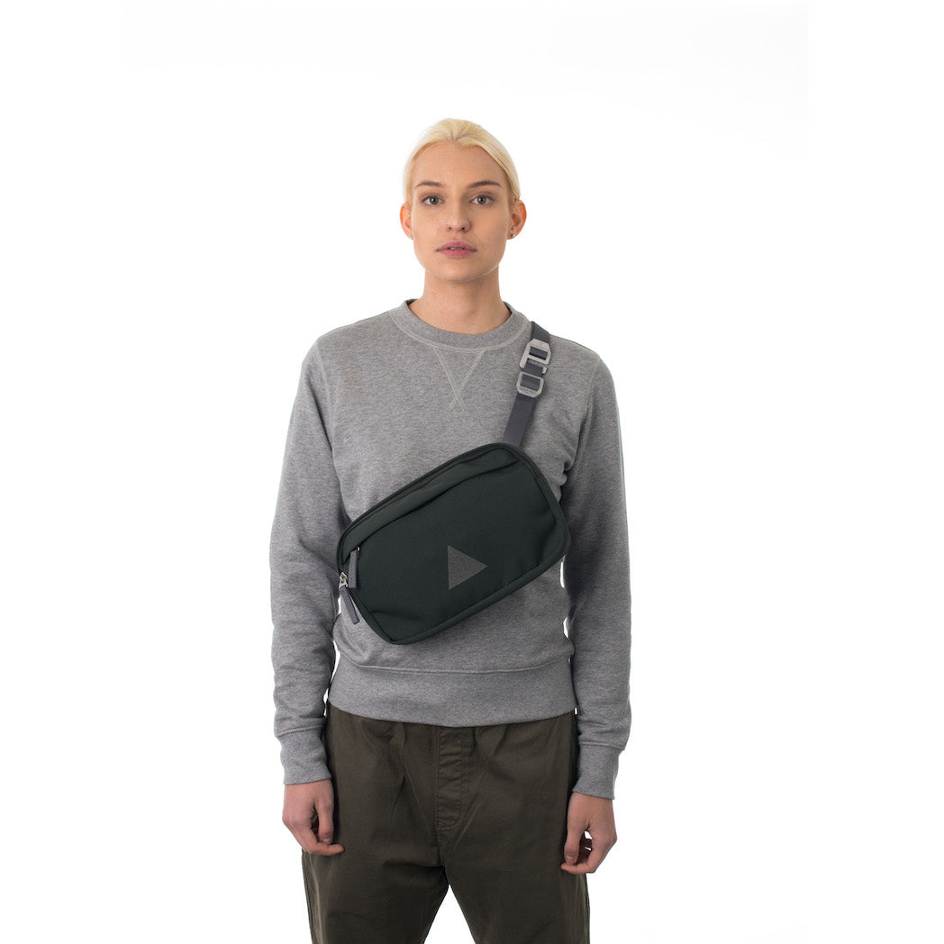 Woman wearing grey cross body bag.