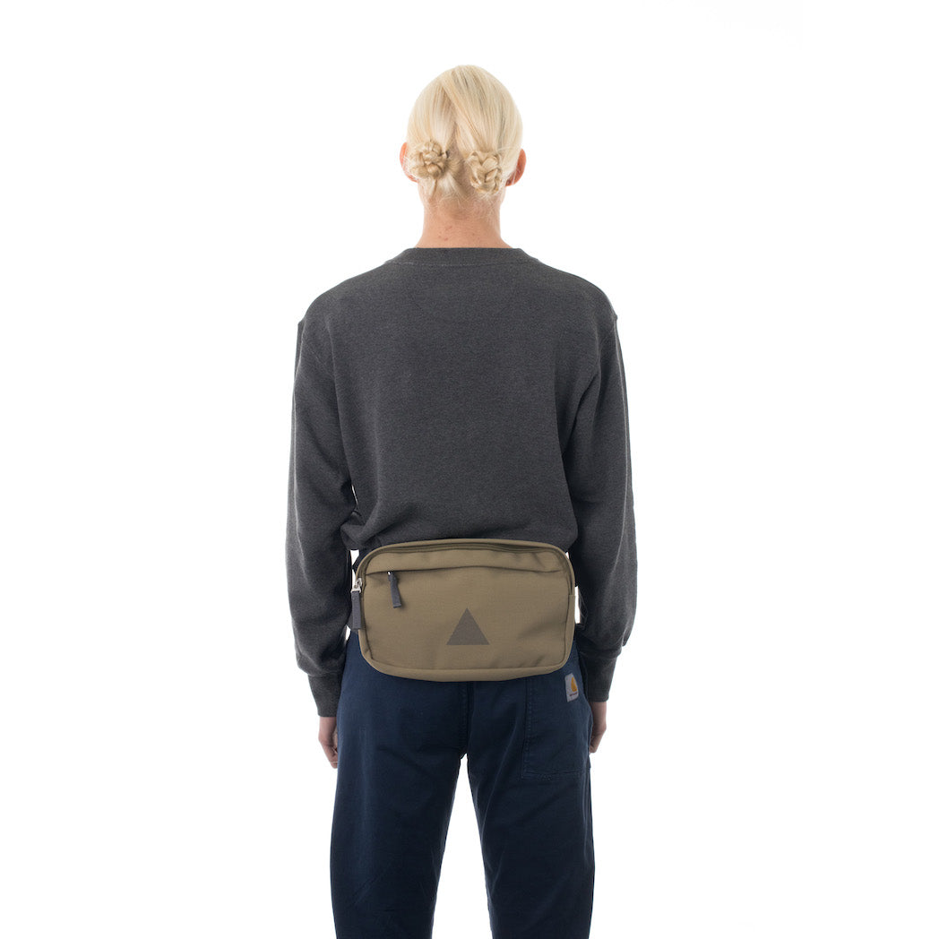 Woman wearing khaki bumbag.