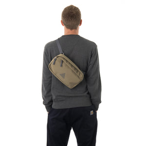 Man wearing khaki bumbag across across back.