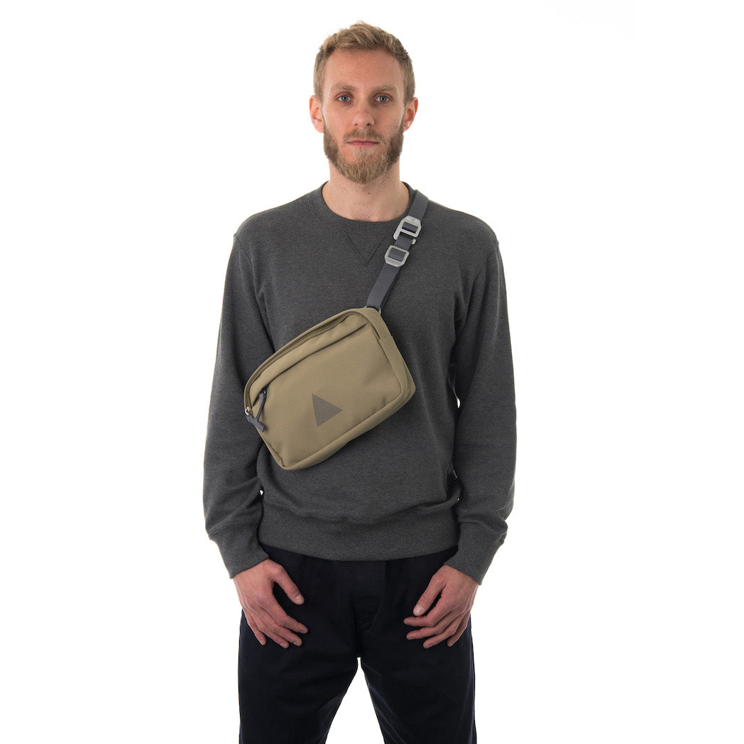 Man wearing khaki cross body bag.