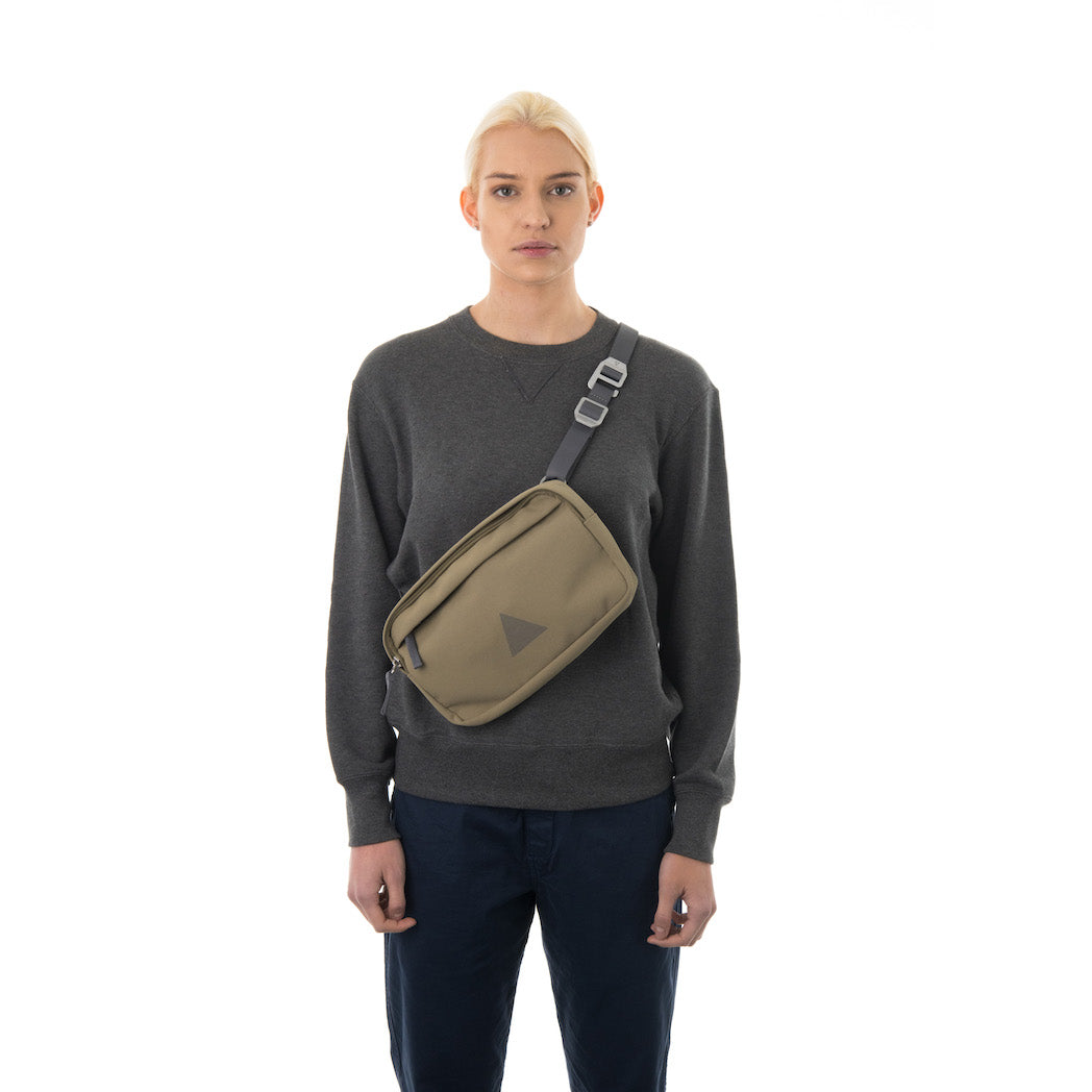 Woman wearing khaki cross body bag.
