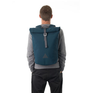 Man carrying blue waterproof rolltop backpack.