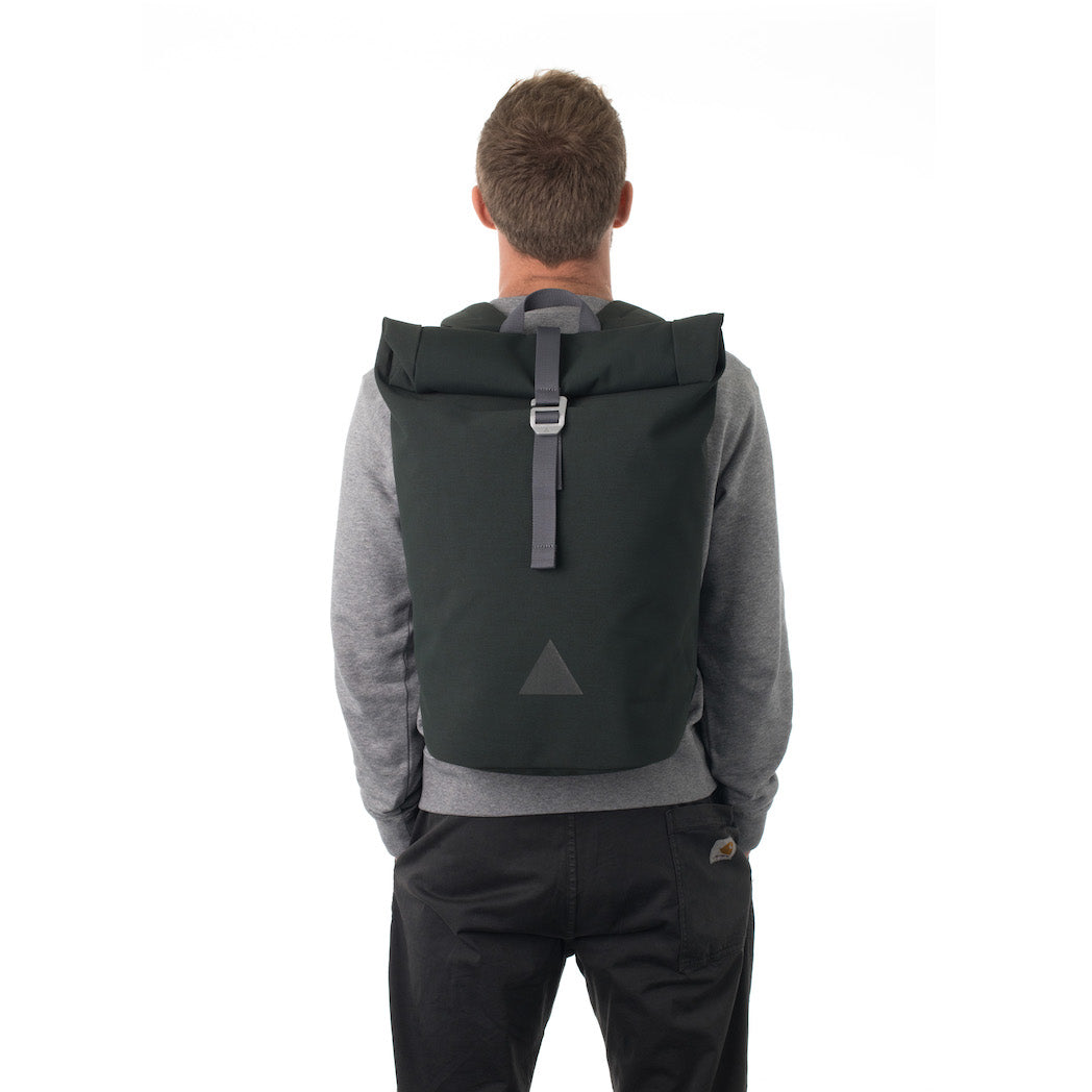 Man carrying grey waterproof rolltop backpack.