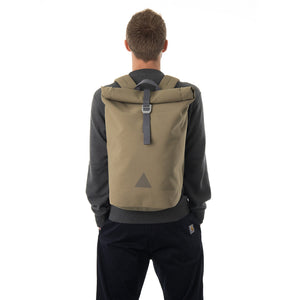 Man carrying khaki waterproof rolltop backpack.