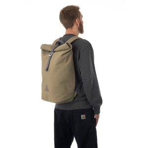Man carrying khaki rolltop backpack.