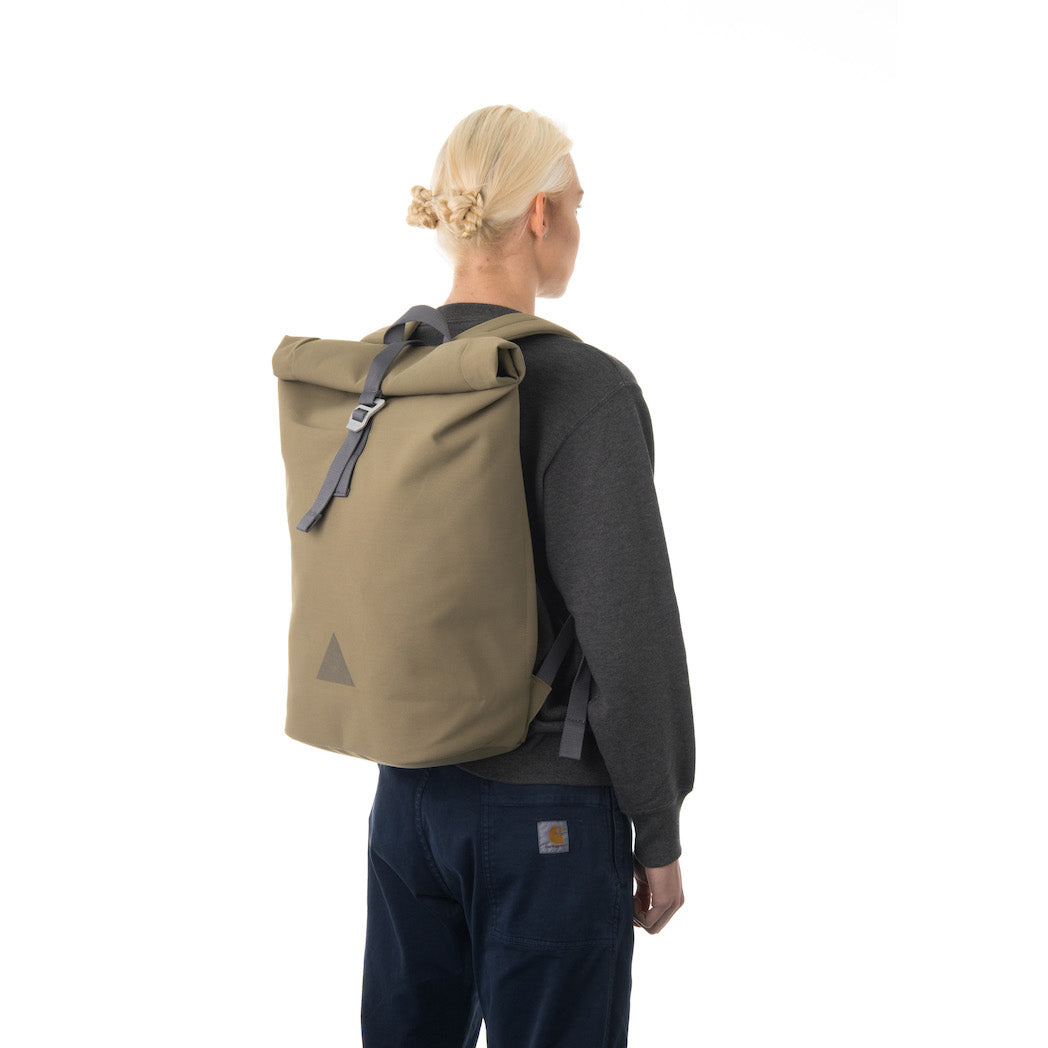 Woman carrying khaki rolltop backpack.