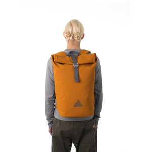Man carrying orange waterproof rolltop backpack.