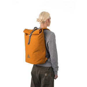 Woman carrying orange rolltop backpack.