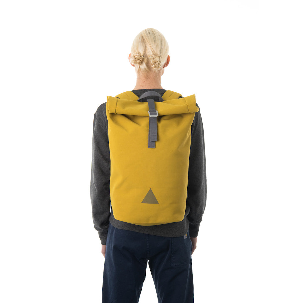 Woman carrying yellow waterproof rolltop backpack.