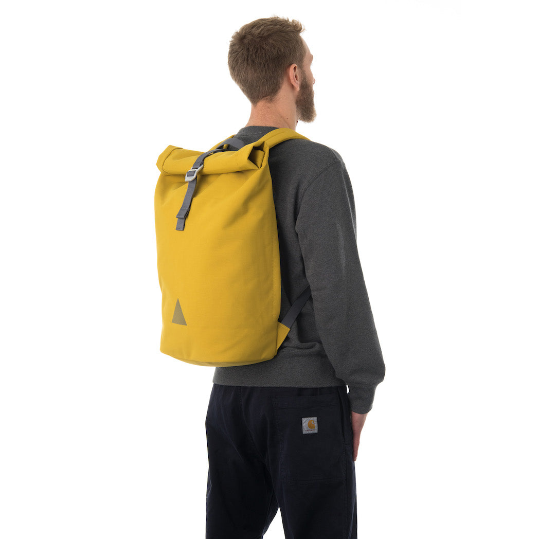 Man carrying yellow rolltop backpack.