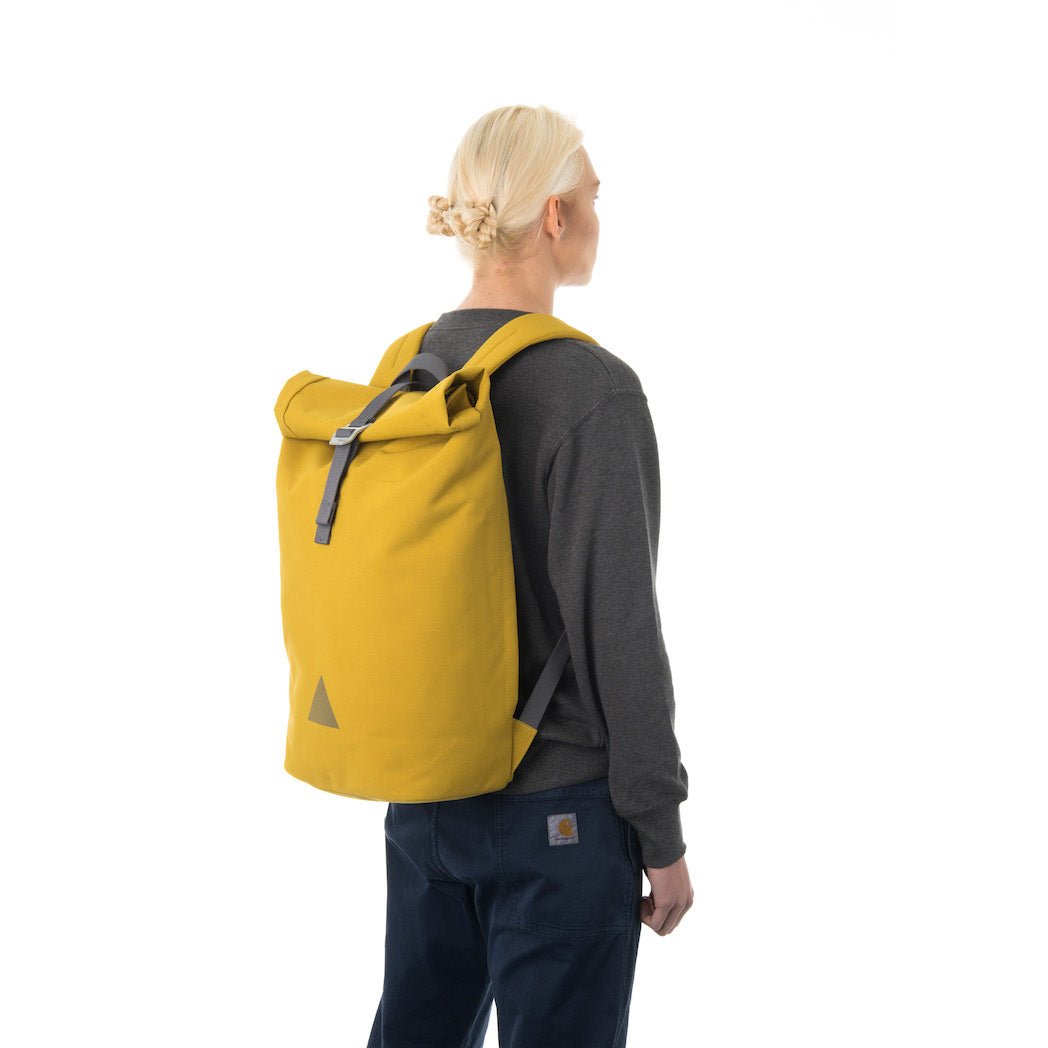 Woman carrying yellow rolltop backpack.