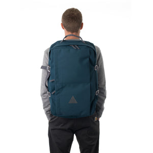 Man carrying blue canvas travel backpack.