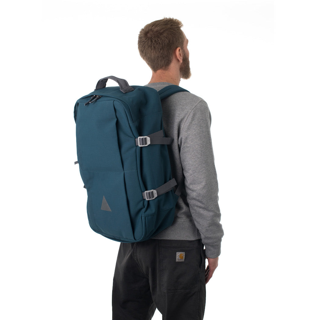 Man carrying blue travel backpack.