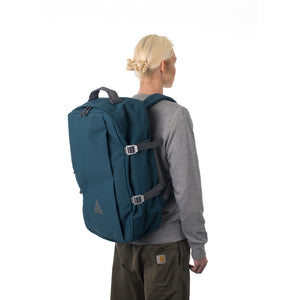 Woman carrying blue travel backpack.
