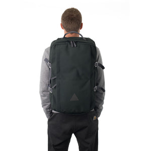 Man carrying grey canvas travel backpack.