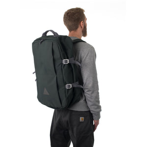 Man carrying grey travel backpack.