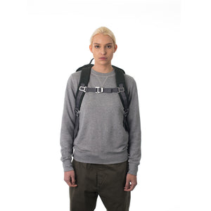 Woman carrying grey travel backpack with padded shoulder straps.