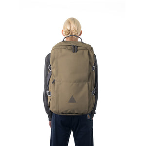 Woman carrying khaki canvas travel backpack.