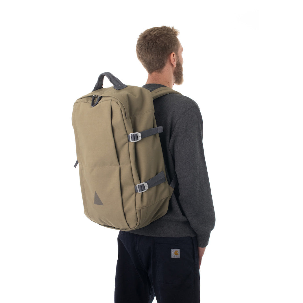 Man carrying khaki travel backpack.