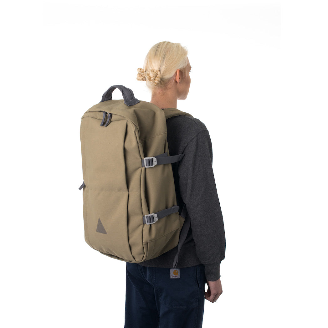 Woman carrying khaki travel backpack.