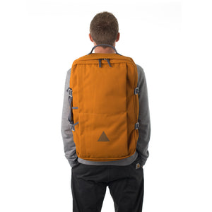 Man carrying orange canvas travel backpack.