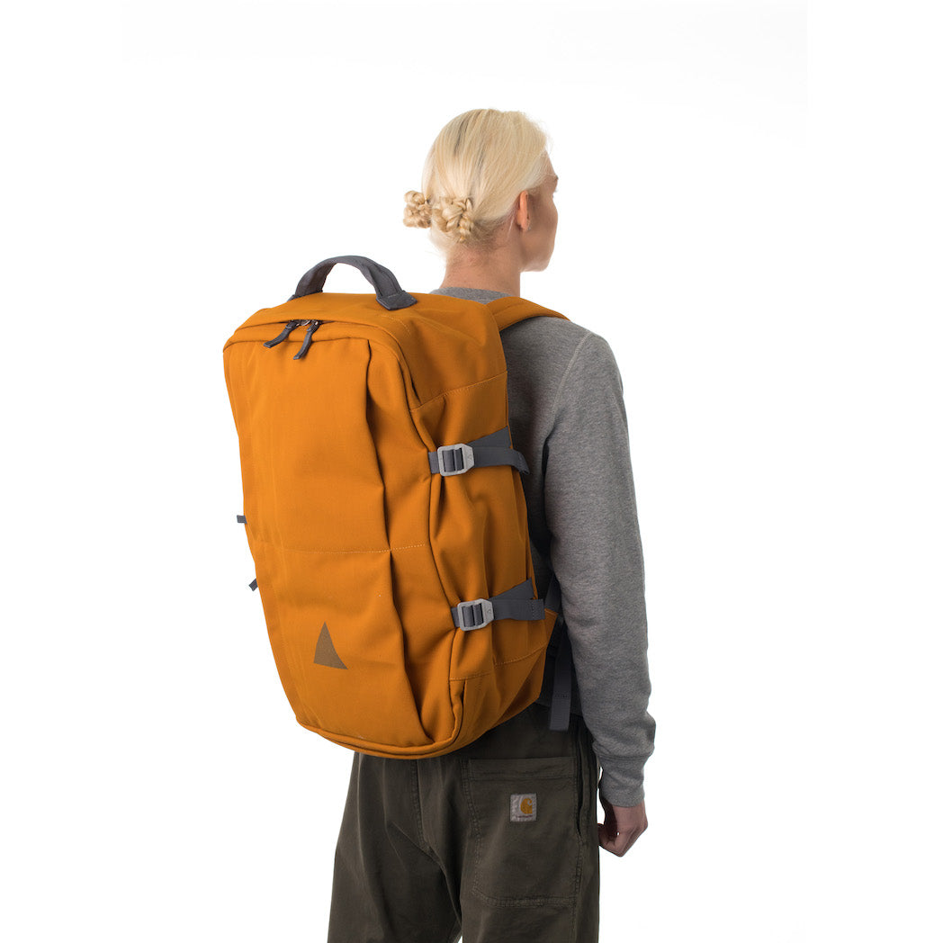 Woman carrying orange travel backpack.