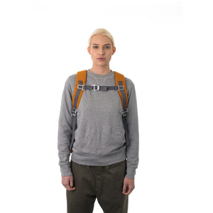 Woman carrying orange travel backpack with padded shoulder straps.