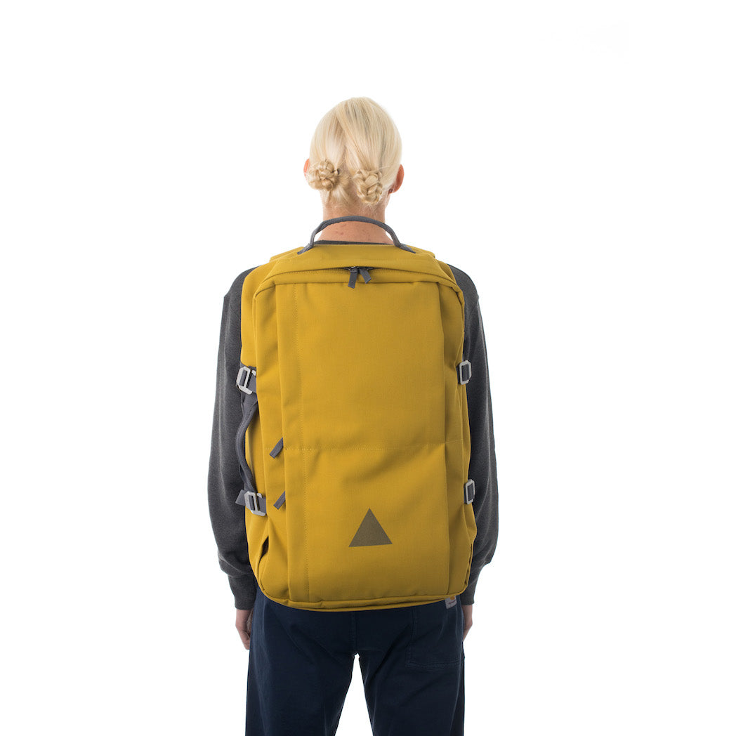 Woman carrying yellow canvas travel backpack.