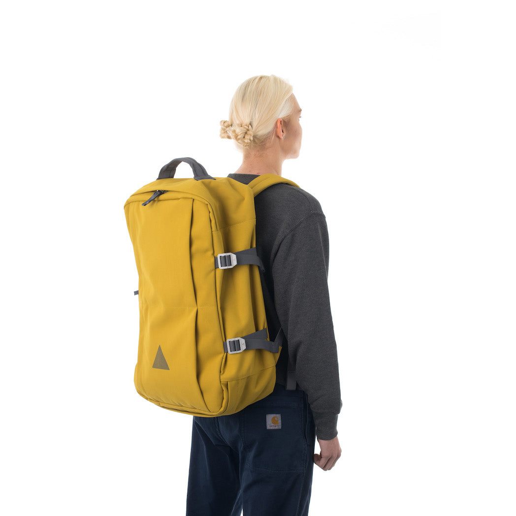 Woman carrying yellow travel backpack.