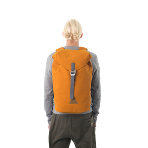 Woman carrying orange waterproof flap backpack.