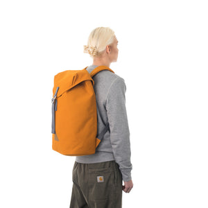 Woman carrying orange flap backpack.