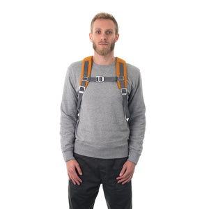 Man carrying orange flap backpack with padded shoulder straps.