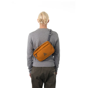 Woman wearing orange bumbag across across back.