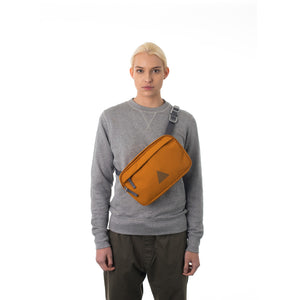 Woman wearing orange cross body bag.