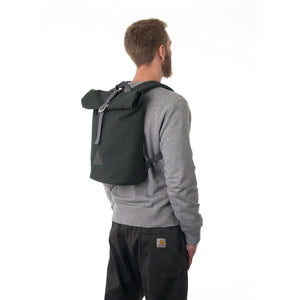 Man carrying grey rolltop backpack.