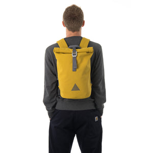 Man carrying yellow waterproof rolltop backpack.