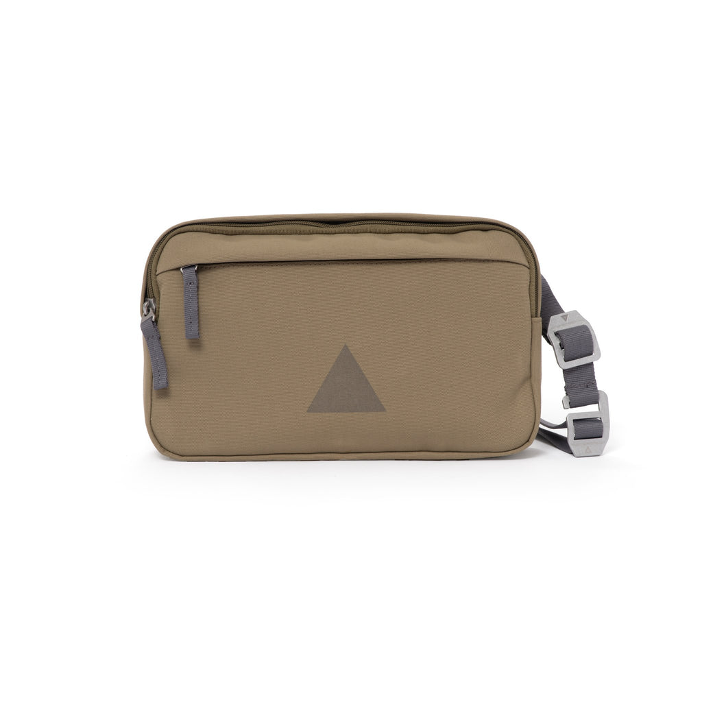 Khaki canvas shoulder bag with front zip pocket, webbing strap and aluminium buckles.