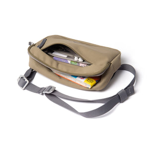 Khaki shoulder bag with front zip open showing map and guidebooks.