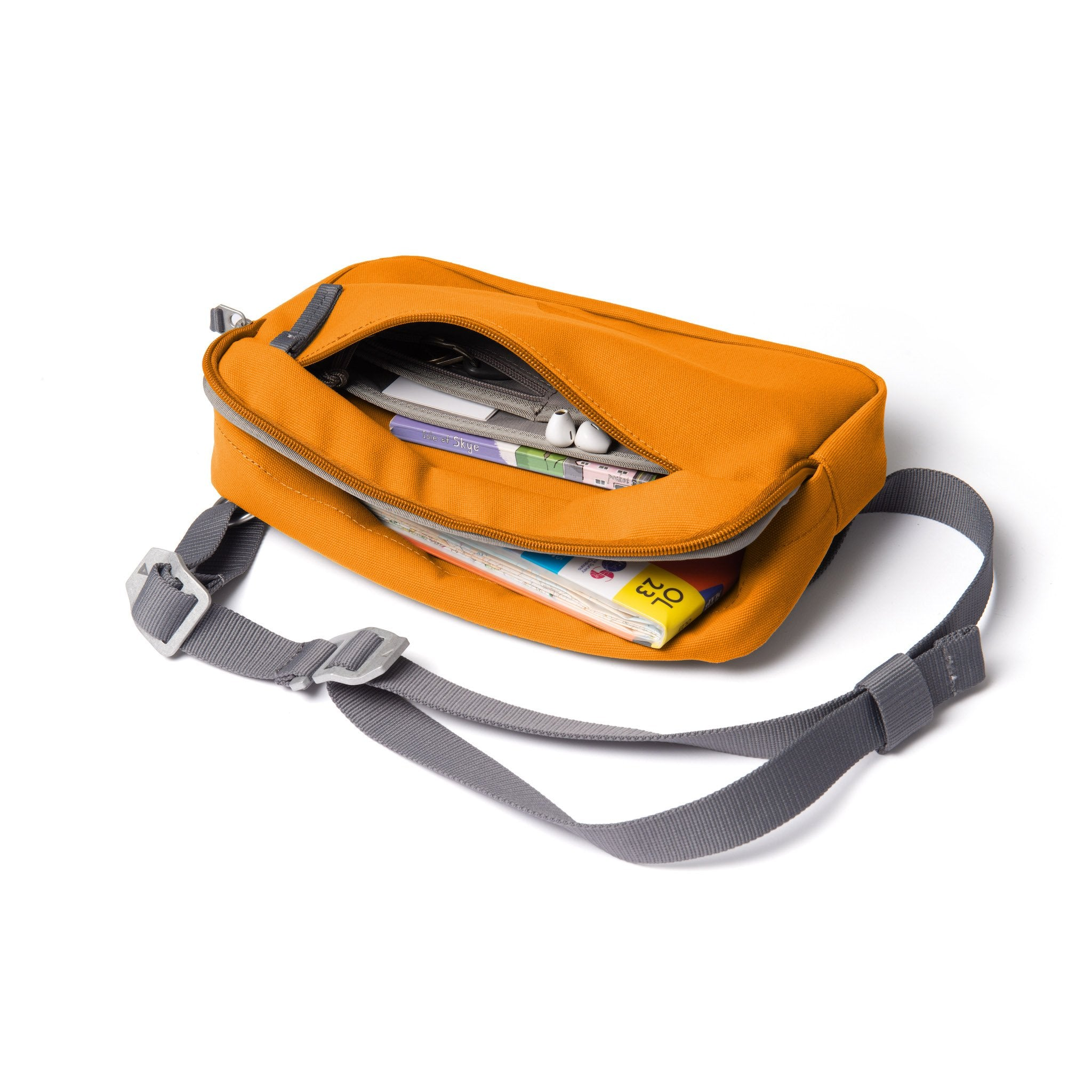 Orange shoulder bag with front zip open showing map and guidebooks.