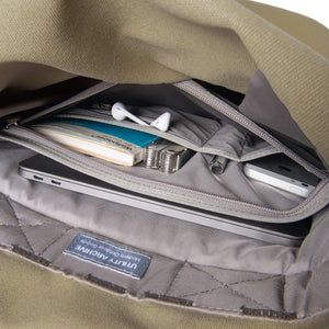 Khaki backpack interior organiser pocket with guidebook and earphones.