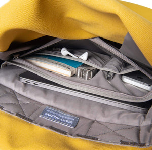 Yellow backpack organiser pocket with guidebook and earphones.