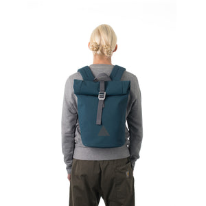 Woman carrying blue waterproof rolltop backpack.