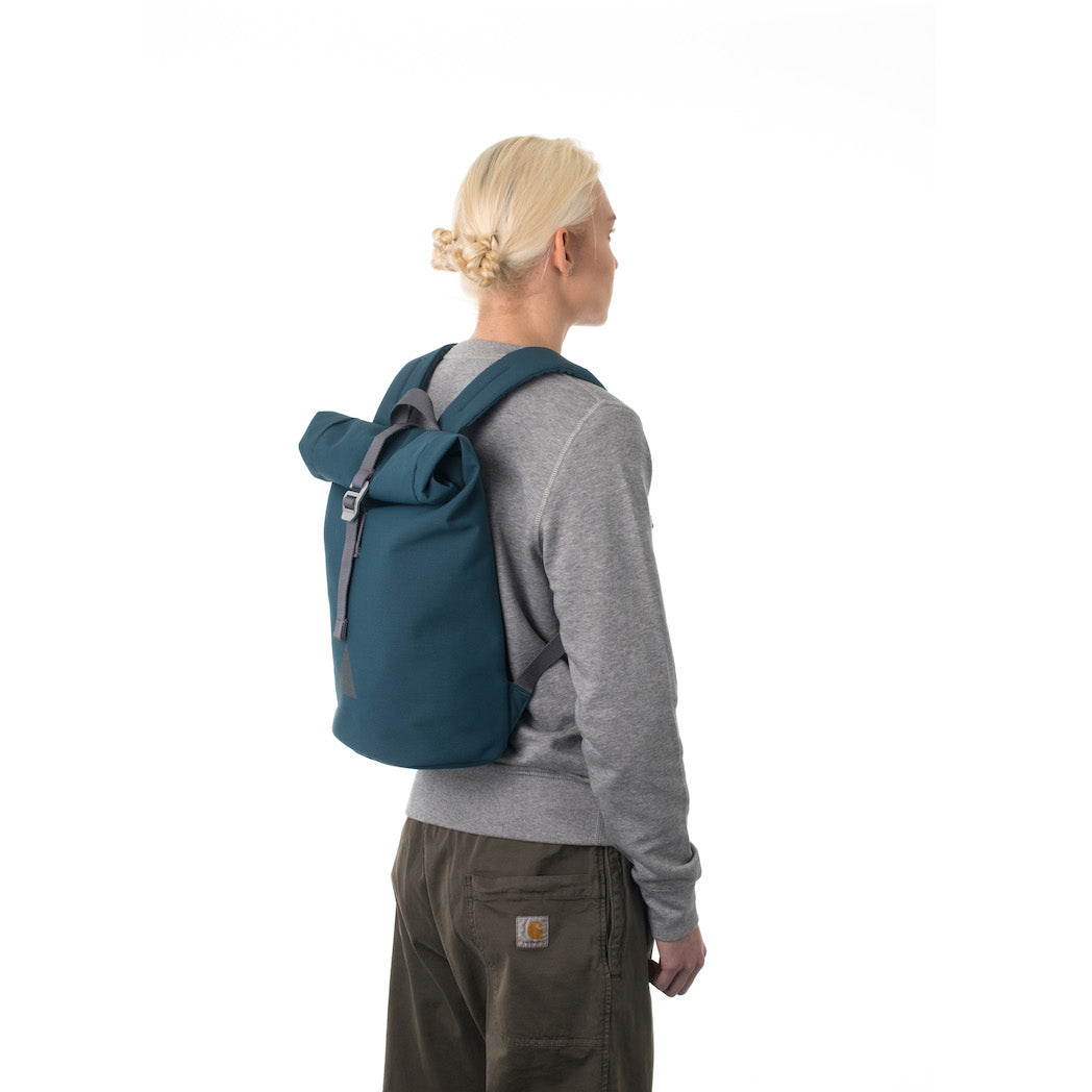 Woman carrying blue rolltop backpack.