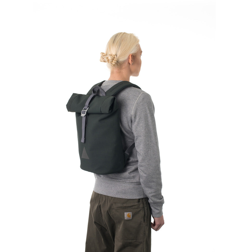 Woman carrying grey rolltop backpack.