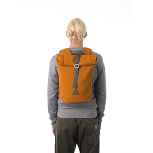 Woman carrying orange waterproof rolltop backpack.