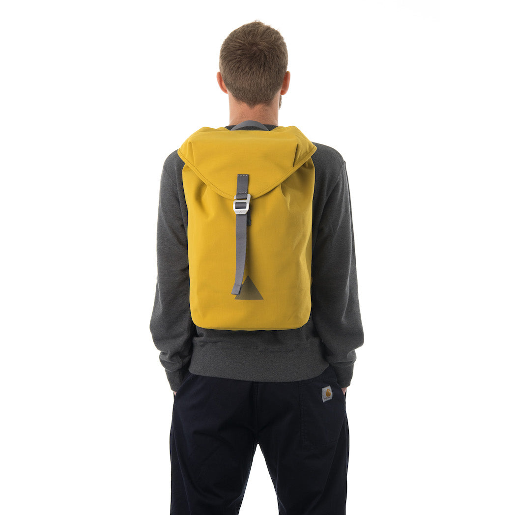 Man carrying yellow waterproof flap backpack.