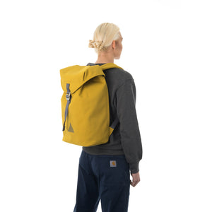 Woman carrying yellow flap backpack.