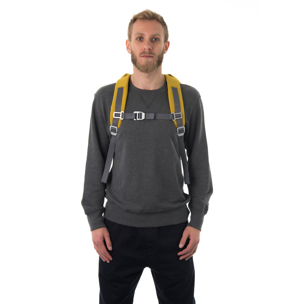 Man carrying yellow backpack with padded shoulder straps.