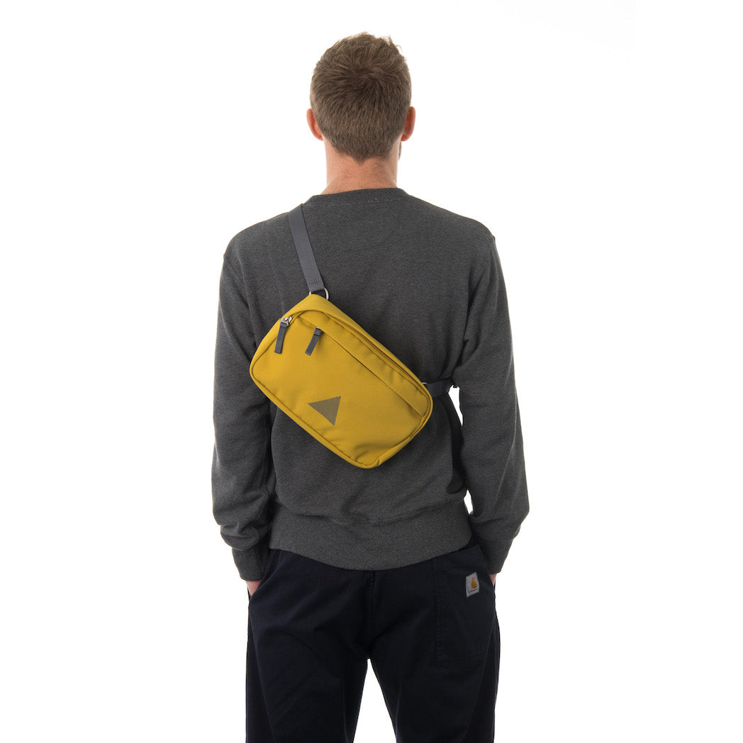 Man wearing yellow bumbag across across back.